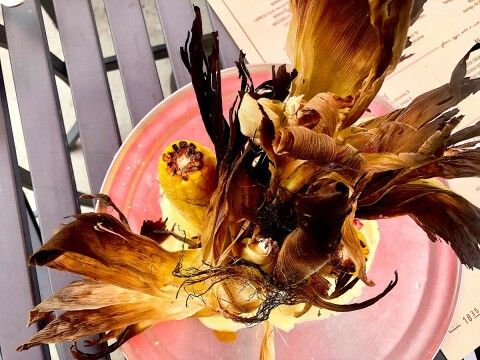 A WITCH'S BROOM?: Roasted corn stands over lemon aioli beneath a headdress designed by the Wicked Witch of the West. Photo credit: Cliff Bostock