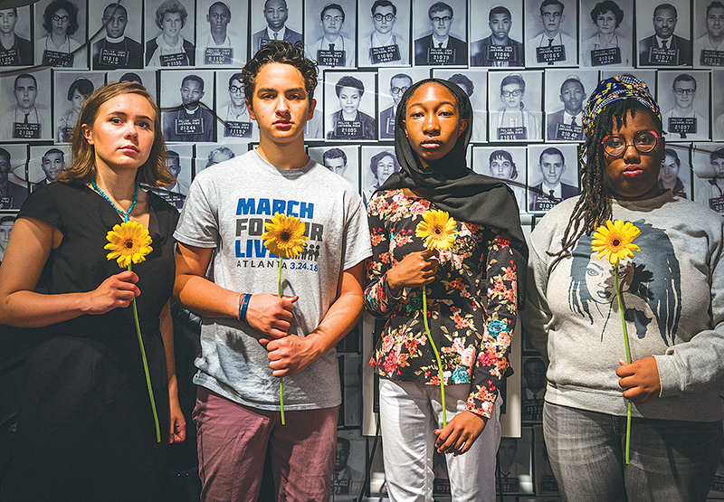 The MFOL 4 pose in front of mugshots of the Freedom Riders who served before them, inside the Center for Civil and Human Rights Museum. Photo by Ian Marceda and Jacob Ross.